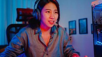 felice asia ragazza professionista giocatore indossare cuffie partecipazione giocare videogioco luci al neon colorate computer nel soggiorno di casa. gioco in streaming di esport online, concetto di attività di quarantena domestica. foto