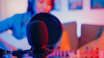felice asia ragazza blogger suona la chitarra e usa il microfono canta canzone registra musica mixer audio sul computer portatile nel soggiorno moderno home studio di notte. creatore di contenuti musicali, tutorial, concetto di trasmissione. foto