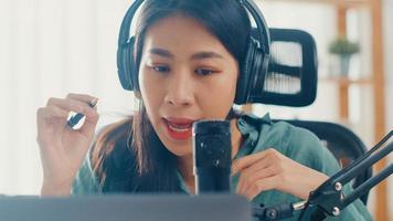 felice ragazza asiatica registra un podcast sul suo computer portatile con cuffie e microfono parla con il pubblico nella sua stanza. il podcaster femminile crea podcast audio dal suo studio di casa, resta al concetto di casa. foto