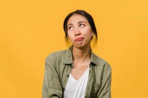 ritratto di giovane donna asiatica con espressione negativa, urla eccitata, pianto emotivo arrabbiato in abbigliamento casual isolato su sfondo giallo con spazio vuoto per la copia. concetto di espressione facciale. foto