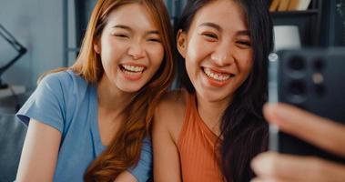 le donne asiatiche adolescenti che si sentono sorridenti si rilassano usando la videochiamata dello smartphone nel soggiorno di casa. videoconferenza allegra delle signore del compagno di stanza con l'amico e la famiglia, concetto di stile di vita della donna a casa. foto
