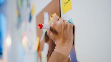 gruppo di giovani uomini d'affari asiatici che discutono riunione di brainstorming aziendale lavorando insieme condividendo dati e scrivendo lavagna sul muro con una nota adesiva in ufficio notturno. concetto di lavoro di squadra del collega. foto