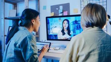 le donne d'affari asiatiche che utilizzano il desktop parlano con i colleghi del piano nella riunione di videochiamata in soggiorno. lavoro da sovraccarico domestico di notte, lavoro a distanza, distanza sociale, quarantena per coronavirus. foto