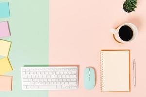 foto piatta creativa della scrivania dell'area di lavoro. scrivania da ufficio vista dall'alto con tastiera, mouse e taccuino nero mockup aperto su sfondo di colore rosa verde pastello. vista dall'alto mock up con la fotografia dello spazio di copia.
