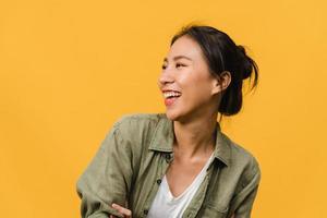 ritratto di giovane donna asiatica con espressione positiva, sorriso ampiamente, vestita con abiti casual su sfondo giallo. felice adorabile donna felice esulta successo. concetto di espressione facciale. foto
