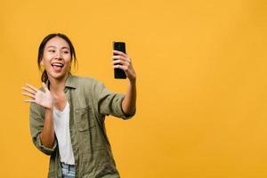 sorridente adorabile femmina asiatica che fa selfie foto su smart phone con espressione positiva in abbigliamento casual e stand isolato su sfondo giallo. felice adorabile donna felice esulta successo.