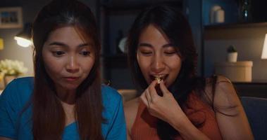 attraenti donne asiatiche con casual goditi un momento felice focus guarda film online intrattenimento su tablet mangia popcorn sito sul divano soggiorno a casa di notte. concetto di quarantena di attività di stile di vita. foto
