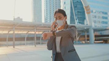 giovane donna d'affari asiatica in abbigliamento da ufficio di moda indossa una maschera medica per il viso parla al telefono mentre cammina da sola all'aperto nella città urbana. affari in movimento, distanza sociale per prevenire la diffusione del concetto di covid-19. foto