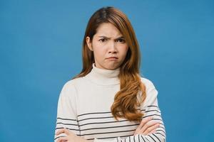 giovane donna asiatica con espressione negativa, urla eccitata, pianto emotivo arrabbiato in abbigliamento casual e guardando la telecamera isolata su sfondo blu. felice adorabile donna felice esulta successo. foto
