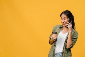 la giovane signora asiatica parla al telefono e tiene la tazza di caffè con espressione positiva, sorride ampiamente, vestita con un panno casual sentendo felicità e stando isolata su sfondo giallo. concetto di espressione facciale. foto