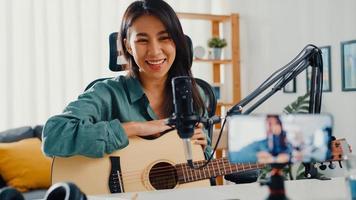 l'influencer di una ragazza asiatica adolescente suona musica per chitarra usa la registrazione del microfono con lo smartphone per il pubblico online ascolta a casa. il podcaster femminile crea podcast audio dal suo studio di casa, resta a casa il concetto. foto