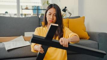 felice giovane donna asiatica che disimballa la scatola e legge le istruzioni per assemblare nuovi mobili decorare la tavola di costruzione della casa con la scatola di cartone nel soggiorno di casa. foto