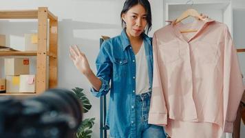 giovane stilista di moda donna asiatica che utilizza il telefono cellulare riceve l'ordine di acquisto e mostra i vestiti che registrano video in streaming live online con la fotocamera. piccolo imprenditore, concetto di consegna del mercato online. foto