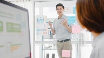 uomini d'affari asiatici che incontrano brainstorming conducendo idee di presentazione aziendale progettano colleghi e indossano una maschera protettiva per il viso nel nuovo ufficio normale. stile di vita e lavoro dopo il virus corona. foto
