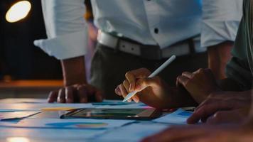 gruppo di giovani creativi asiatici in abbigliamento casual intelligente che discutono di idee per riunioni di brainstorming aziendale progetto di progettazione di software per applicazioni mobili in un moderno ufficio notturno. concetto di lavoro di squadra del collega. foto