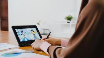 asia signora musulmana che utilizza tablet digitale parla con un collega del piano tramite videochiamata brainstorming riunione online mentre lavora in remoto da casa in soggiorno. distanziamento sociale, quarantena per il virus corona. foto