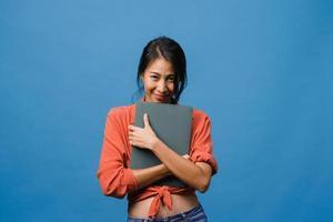 la giovane signora asiatica tiene il portatile con un'espressione positiva, sorride ampiamente, vestita con abiti casual sentendo felicità e stando isolato su sfondo blu. felice adorabile donna felice esulta successo. foto