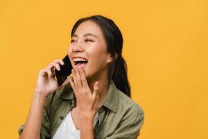 la giovane signora asiatica parla al telefono con un'espressione positiva, sorride ampiamente, vestita con abiti casual sentendo felicità e stando isolata su sfondo giallo. felice adorabile donna felice esulta successo. foto