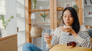 giovane donna malata dell'Asia che tiene la pillola bicchiere d'acqua prendere la medicina sedersi sul divano a casa. ragazza che prende medicine dopo l'ordine del medico, quarantena a casa, concetto di quarantena di allontanamento sociale del coronavirus. foto