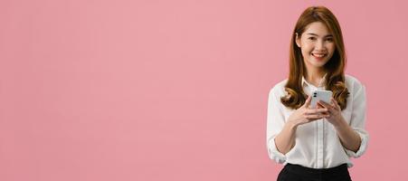 sorpresa giovane signora asiatica che utilizza il telefono cellulare con espressione positiva, sorride ampiamente, vestita con abiti casual e guardando la telecamera su sfondo rosa. sfondo banner panoramico con spazio di copia. foto