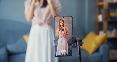 felice giovane ragazza asiatica blogger davanti alla fotocamera del telefono registra video divertiti con contenuti di danza nel soggiorno di casa. concetto di pandemia di coronavirus a distanza sociale. libertà e concetto di stile di vita attivo foto