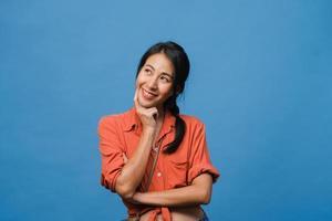 ritratto di giovane donna asiatica con espressione positiva, sorriso ampiamente, vestito con abiti casual su sfondo blu. felice adorabile donna felice esulta successo. concetto di espressione facciale. foto