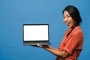 la giovane donna asiatica mostra lo schermo del laptop vuoto con un'espressione positiva, sorride ampiamente, vestita con abiti casual sentendo felicità isolata su sfondo blu. computer con schermo bianco in mano femminile. foto