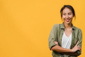 ritratto di giovane donna asiatica con espressione positiva, braccio incrociato, sorriso ampiamente, vestita con un panno casual su sfondo giallo. felice adorabile donna felice esulta successo. concetto di espressione facciale. foto