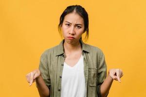 la giovane donna asiatica mostra qualcosa di straordinario nello spazio vuoto con espressione negativa, urla eccitate, pianto emotivo arrabbiato guardando la telecamera isolata su sfondo giallo. concetto di espressione facciale. foto