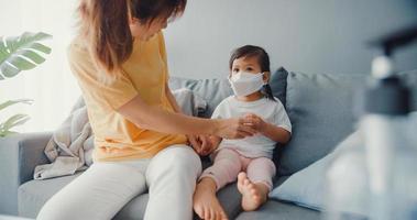 felice allegra famiglia asiatica mamma che indossa una maschera protettiva si siede sul divano nel soggiorno di casa. trascorrere del tempo insieme, distanza sociale, quarantena per la prevenzione del coronavirus, concetto di assistenza sanitaria. foto