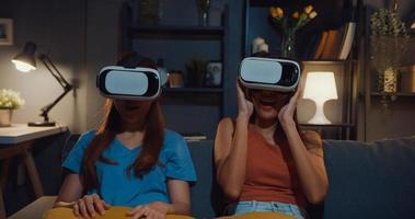 attraenti donne asiatiche godono di un felice momento di shopping online con occhiali per realtà virtuale sito di cuffie sul divano del soggiorno di casa durante la notte buia. utilizzando con l'auricolare vr goggles per l'ora del film. foto