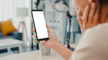 la giovane donna asiatica usa lo smartphone con lo schermo bianco vuoto finto display per il testo pubblicitario mentre lavora in modo intelligente da casa in soggiorno. tecnologia chiave di crominanza, concetto di design di marketing. foto