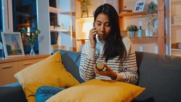 giovane donna asiatica malata tenere la medicina sedersi sul divano usa lo smartphone per consultare il medico a casa la notte. la ragazza prende la medicina dopo l'ordine del medico, la quarantena a casa, il concetto di coronavirus a distanza sociale. foto