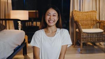 allegra giovane signora asiatica che si sente felice sorridere e guarda la fotocamera usando il telefono effettua una videochiamata dal vivo nel soggiorno di casa la notte. distanziamento sociale, quarantena per coronavirus. vista webcam ravvicinata. foto