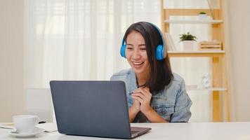 abbigliamento casual da donna d'affari freelance che utilizza laptop videoconferenza chiamata di lavoro con il cliente sul posto di lavoro nel soggiorno di casa. felice giovane ragazza asiatica rilassarsi seduto sulla scrivania fare un lavoro in internet. foto