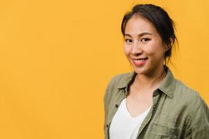 giovane donna asiatica con espressione positiva, sorriso ampiamente, vestita con abiti casual e guardando la telecamera su sfondo giallo. felice adorabile donna felice esulta successo. concetto di espressione facciale. foto