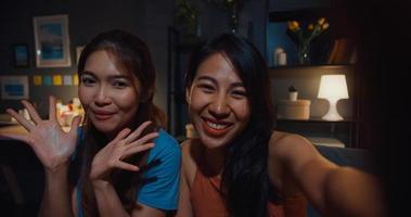 le donne adolescenti asiatiche si sentono felici e sorridenti selfie e guardano la telecamera con relax nel soggiorno a casa la notte. Videochiamata allegra delle signore del compagno di stanza con l'amico e la famiglia, concetto di stile di vita della donna a casa. foto