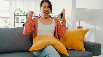 la bella signora asiatica si siede sul divano si sente eccitata con grandi notizie a casa. colloquio di successo, conseguimento di laurea, accettazione di incontri di appuntamenti, approvazione del credito di avvio, test di superamento, datore di lavoro accetta il concetto di lavoro. foto