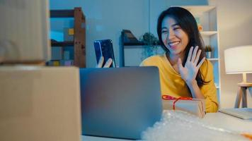 la giovane donna d'affari asiatica usa lo smartphone riceve l'ordine di acquisto e mostra la confezione del prodotto al video del cliente in diretta streaming online nel negozio di notte. piccolo imprenditore, concetto di consegna del mercato online. foto