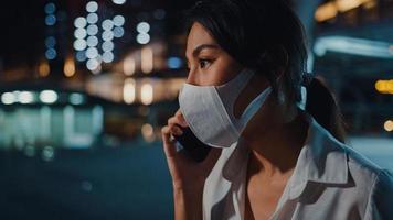 seria insoddisfatta sconvolta giovane donna d'affari asiatica indossa una maschera medica per il viso parla via telefono mentre cammina da sola all'aperto nella notte urbana della città. affari in movimento, distanziamento sociale per prevenire la diffusione del covid-19. foto