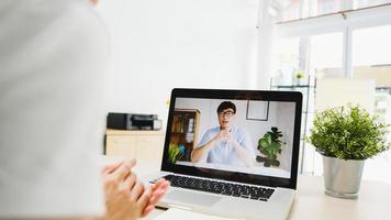 asia imprenditrice utilizzando laptop parlare con i colleghi del piano in videochiamata riunione mentre si lavora da casa in soggiorno. autoisolamento, distanziamento sociale, quarantena per la prevenzione del virus corona. foto