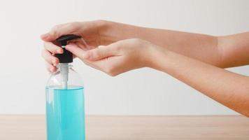 donna asiatica che usa disinfettante per le mani in gel alcolico per lavare le mani per proteggere il coronavirus. la femmina spinge la bottiglia di alcol per pulire la mano per l'igiene quando il distanziamento sociale rimane a casa e il tempo di autoquarantena. foto