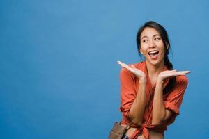 la giovane signora asiatica si sente felice con l'espressione positiva, gioiosa sorpresa funky, vestita con un panno casual isolato su sfondo blu. felice adorabile donna felice esulta successo. espressione facciale. foto