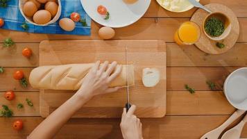 le mani della giovane donna asiatica chef tenere il coltello tagliare il pane integrale su tavola di legno sul tavolo della cucina in casa. produzione di pane fresco fatto in casa, alimentazione sana e concetto di panetteria tradizionale. colpo di vista dall'alto. foto