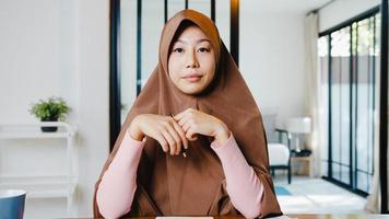 asia la signora musulmana indossa l'hijab utilizzando il computer portatile parla con i colleghi del piano nella riunione di videochiamata mentre lavora in remoto da casa in soggiorno. distanziamento sociale, quarantena per il virus corona. foto