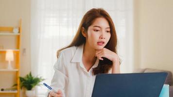 donna d'affari asiatica che utilizza laptop parla con i colleghi del piano in videochiamata mentre lavora in modo intelligente da casa in soggiorno. autoisolamento, distanziamento sociale, quarantena per la prevenzione del coronavirus. foto