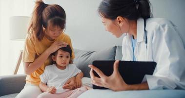giovane donna pediatra asiatica medico e bambina paziente utilizzando tablet digitale condividendo buone notizie di test di salute con mamma felice sedersi sul divano in casa. assicurazione medica, visita il concetto di paziente a casa. foto