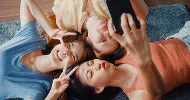sopra vista primo piano gruppo di donne asiatiche con felicità godere momento tenere smartphone sorridente scattare ricordi foto sdraiato sul tappeto nel pavimento soggiorno a casa. concetto di quarantena di attività di stile di vita.