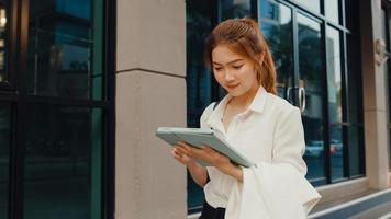 giovane imprenditrice asiatica di successo in abiti da ufficio di moda utilizzando tablet digitale e digitando un messaggio di testo mentre si cammina da soli all'aperto nella città moderna urbana al mattino. concetto di affari in movimento. foto