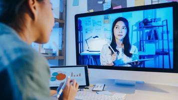 donna d'affari asiatica che utilizza il desktop parla con i colleghi del piano nella riunione di videochiamata in soggiorno. lavoro da sovraccarico domestico di notte, lavoro a distanza, distanza sociale, quarantena per coronavirus. foto